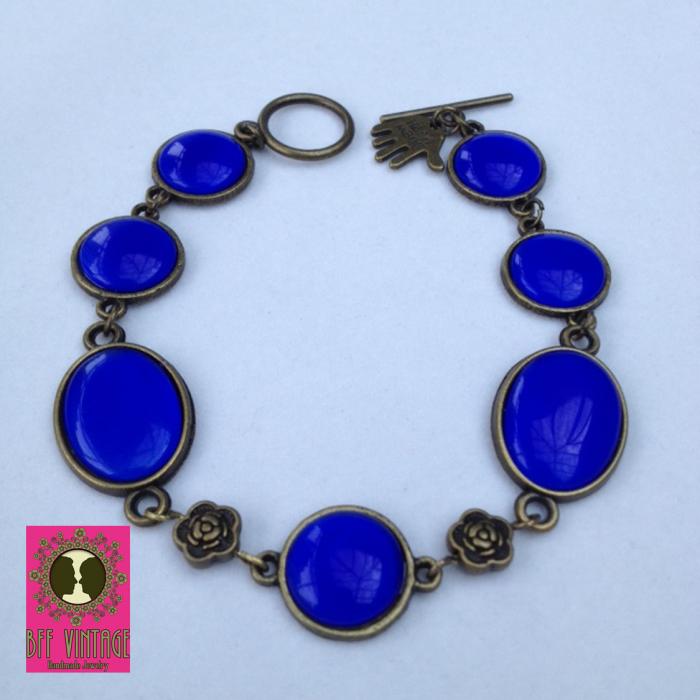 Bronskleurige armband met bronzen bloemetjes en koningsblauwe cateyes