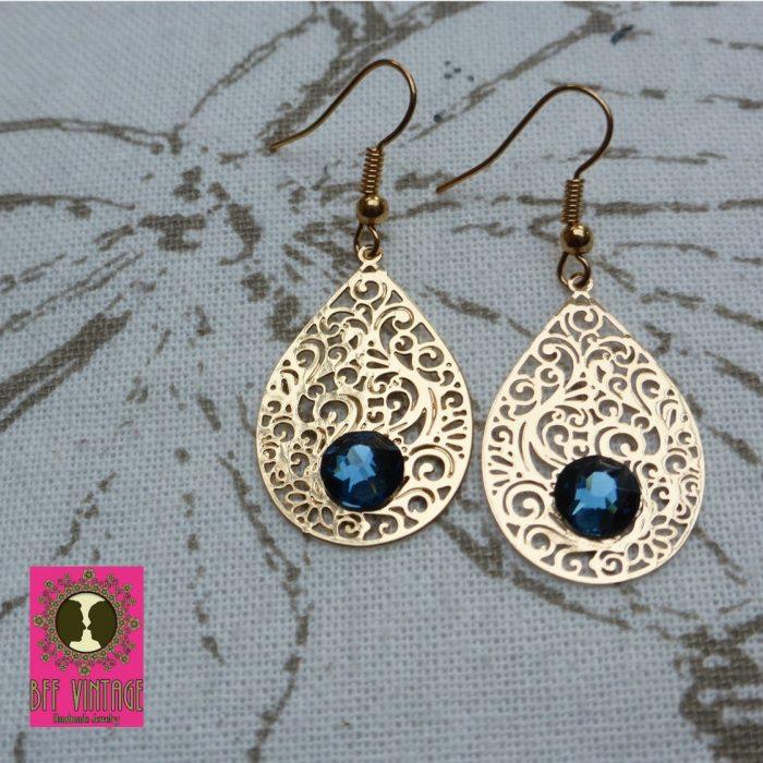 Goudkleurige oorbellen met DQ druppelfiligraanhangers en blauwe Swarovski