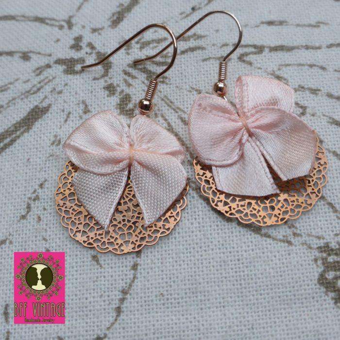 Rosékleurige oorbellen met ronde DQ filigraanhangers en roze strikken