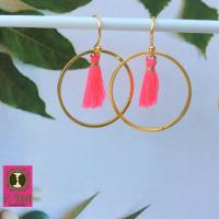 Goudkleurige oorbellen met hot pink kwastjes in een grote ring